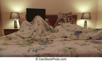 couple lying together on bed at night woman reading magazine...