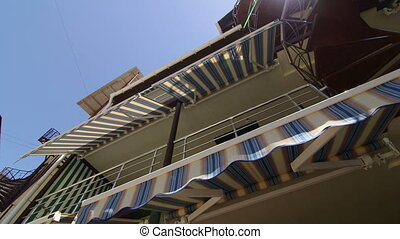 Summer hotel exterior with retractable striped awnings and spiral staircase
