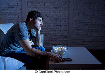 television addict man sitting on sofa watching TV eating...