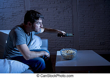 television addict man sitting on home sofa watching TV...
