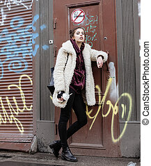young pretty stylish teenage girl outside in city wall with...