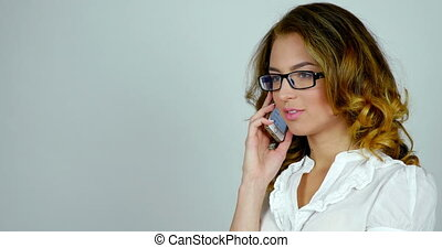 Young attractive woman talks on telephone and moves her...