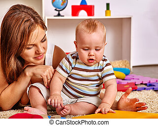 Kid with mother baby boy playing with puzzle toys on floor.