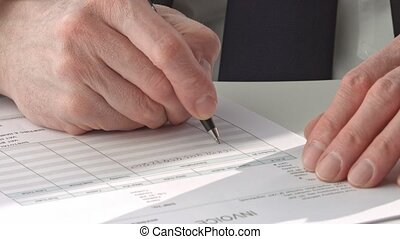 male hand in suit filling in invoice paper close up