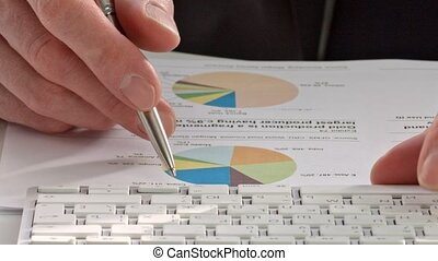 Businessmans hand showing diagram on report with pen -...