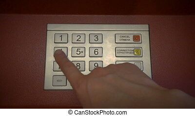 Finger entering secret pin number at ATM
