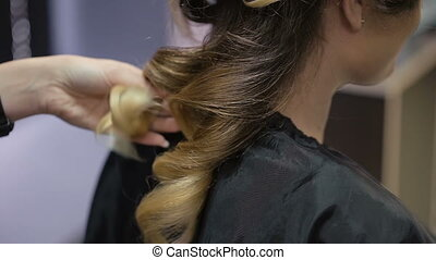Woman in a beauty salon. hairstyles wizard makes client...