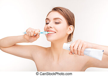Beauty portrait of happy young woman brushing her teeth