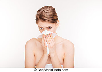 Sad ill young woman sneezing and using paper handkerchief