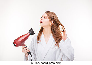 Pretty smiling young woman in bathrobe using hair dryer -...