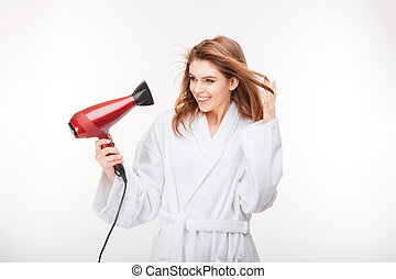 Cheeful lovely young woman drying her hair with dryer -...