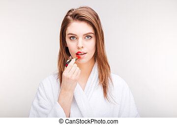 Beautiful sensual woman trying red lipstick on half of lips...