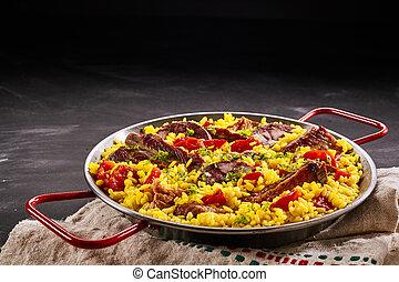 Rustic metal dish of paella al homo - Rustic metal dish of...