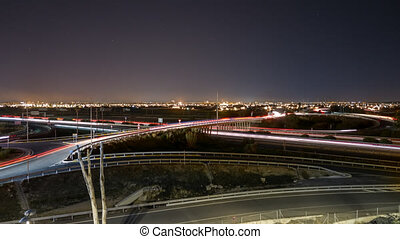 Time lapse busy light trail traffic, city skyline and stars...