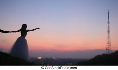 Silhouette of bride on the hill stretching hands to the sky