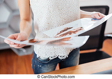 Young woman photographer holding photos of model in office