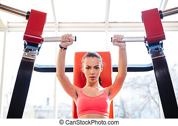 Young sportswoman doing exercises in gym - Attractive...