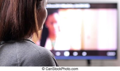 Watching tv with remote control - Young woman with remote...