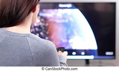 Watching tv with remote control - Young woman watching smart...