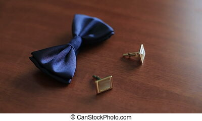 Blue silk bowtie and cufflinks on wooden background close up