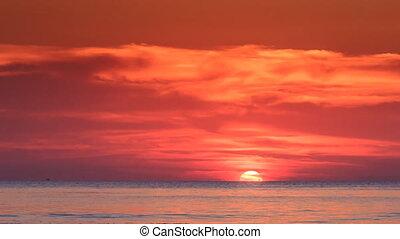 Red Sunset Sun Half behind Skyline Sunlight Reflection on...