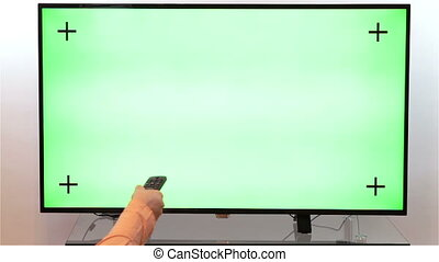 Surfing television channels green - Woman hand with TV...