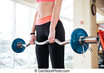 Barbell holded by young sportswoman working out in gym -...
