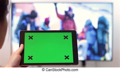 Woman with tablet pc green screen - Woman watches television...
