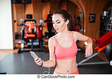 Smiling woman athlete with earphones using smartphone in gym...