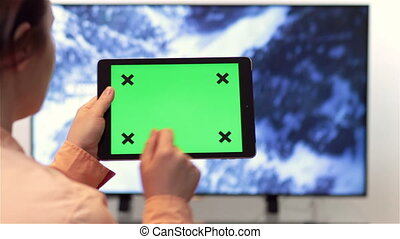 Tablet pc and smart TV green screen - Woman watches...