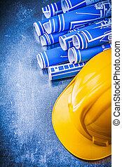 Blue engineering drawings yellow building helmet on...
