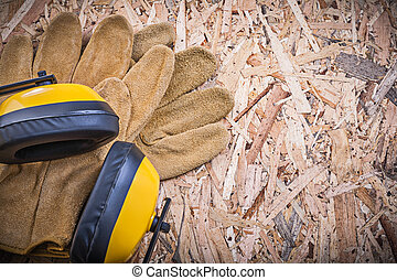 Safety leather gloves earmuffs on chipboard