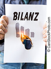 businessman is holding a burning paper with german word...
