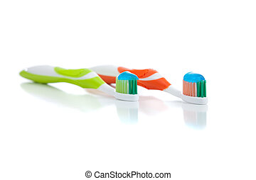 Green and orange toothbrushes on a white background