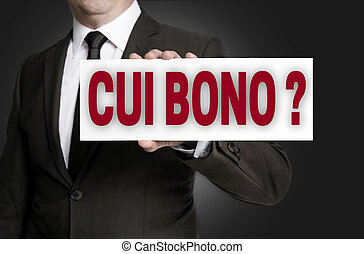 cui bono sign is held by businessman background.