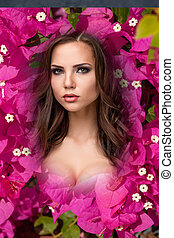 The beauty young woman with flowers of pink bougainvillea -...