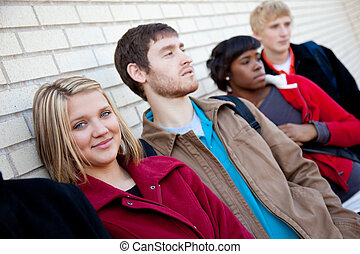 Multi-racial college students against a brick wall