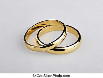 Two well used Golden Wedding Rings on gray background