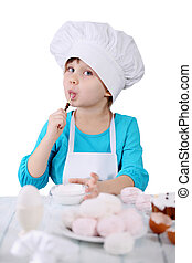girl licks a spoon - little girl in a cap Chef preparing...