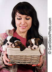 woman holding a basket of puppies