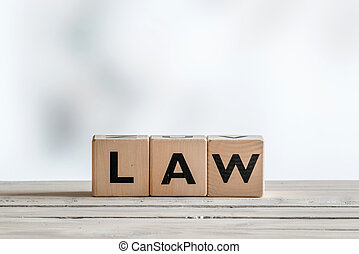 Law sign on a wooden desk on white background