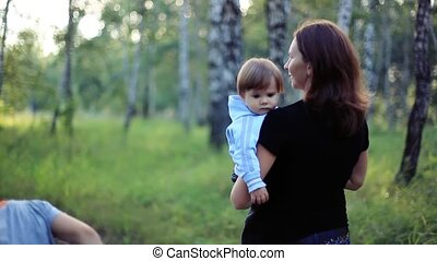Cheerful mother and child walking together outdoors in park...