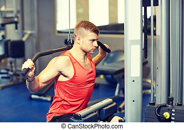 man flexing muscles on cable machine gym - sport, fitness,...