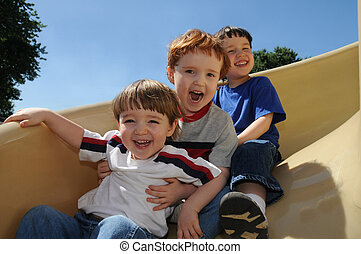 Sliding fun - Three brothers have a great time sliding down...