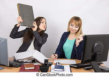 The girl in the office threatens to hit another folder...