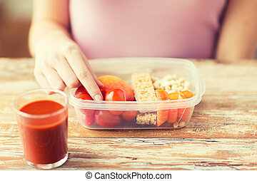 close up of woman with vegetarian food in box