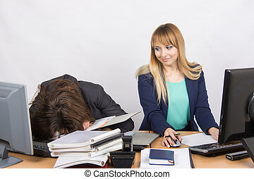 Female colleagues in the office, one had fallen asleep on a pile of folders, and the second looked at her