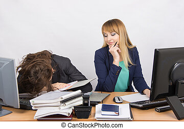 Female colleagues in the office, one had fallen asleep on a pile of folders, the second with a sneer looks at her