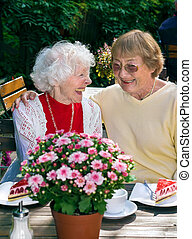 Two elderly ladies enjoying coffee together. - Two elderly...