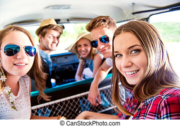 Teenage boys and girls inside an old campervan, roadtrip -...